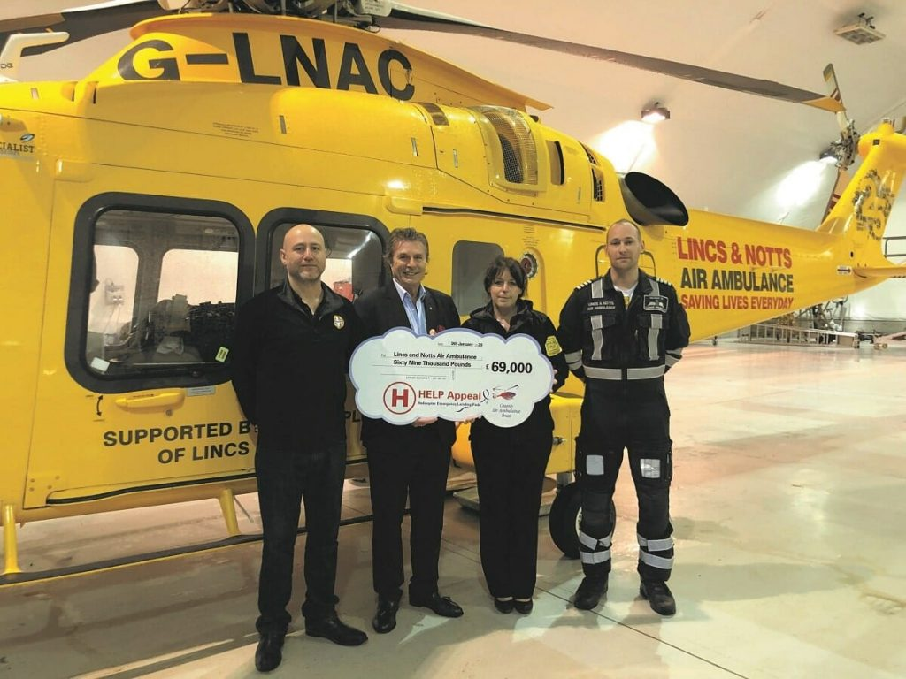 PROUD: Robert Bertram, Chief Executive of the HELP Appeal, with members of the crew from the Lincs & Notts Air Ambulance and their iconic Agusta Westland 169 helicopter, at the upgraded facility at RAF Waddington.